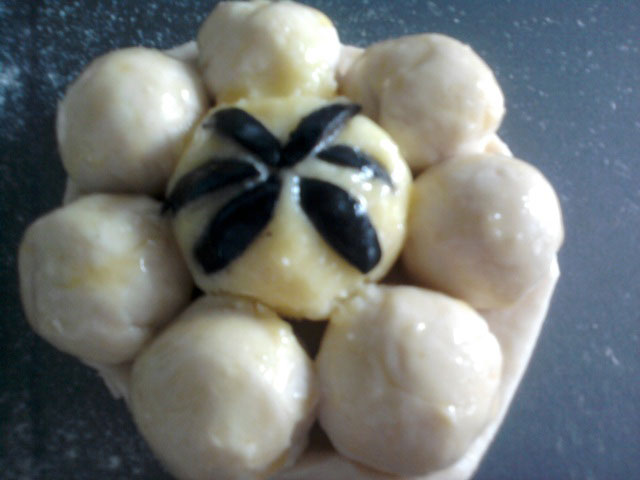 Украсить пирожки оливками и смазать яйцом